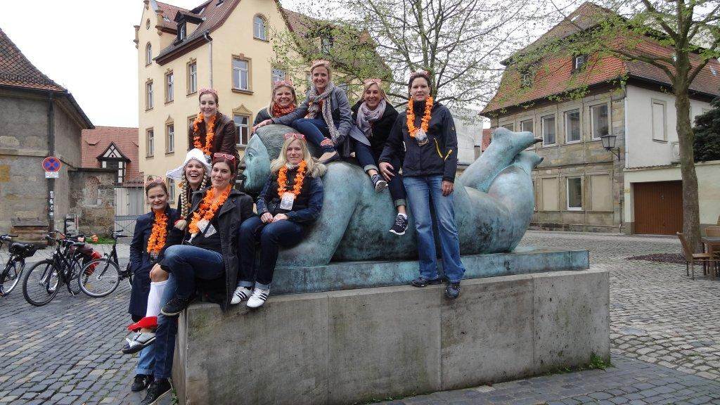 "A stag party bike tour group exploring Bamberg's historic Old Town have stopped for a rest on Botero's ""Blunzn"" (Franconian for ""fat lady."")"